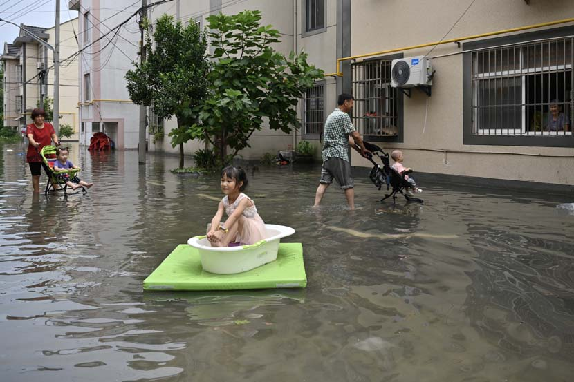 A girl sits in a bathtub floating on the floodwater in Pinghu, Zhejiang province, Aug. 5, 2020. The area was inundated after Typhoon Hagupit struck China's southeastern coastline. Jim/People Visual