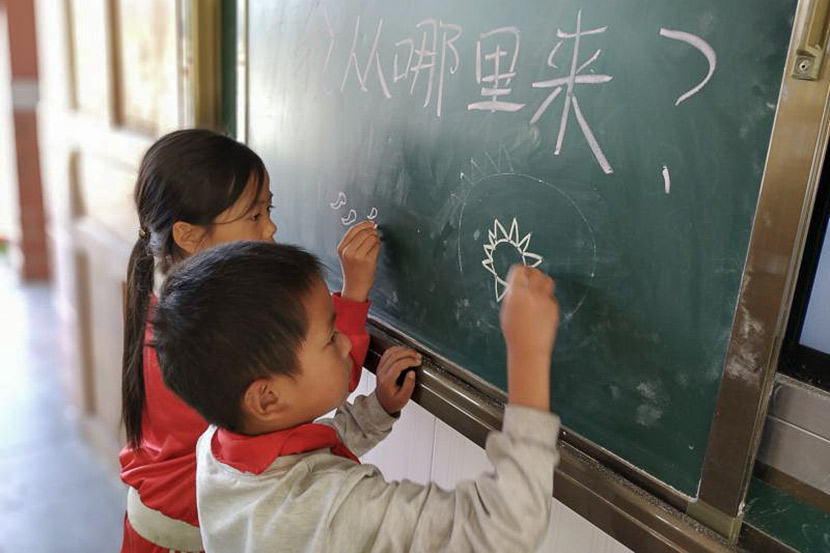 Children draw sperm and eggs on the blackboard during a sex education class at a rural primary school. Courtesy of You&Me