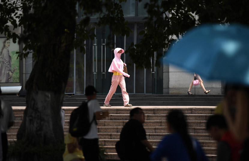 A woman in sun-protection gear walks along a road in Chongqing, Aug. 10, 2020. Chen Chao/CNS/People Visual