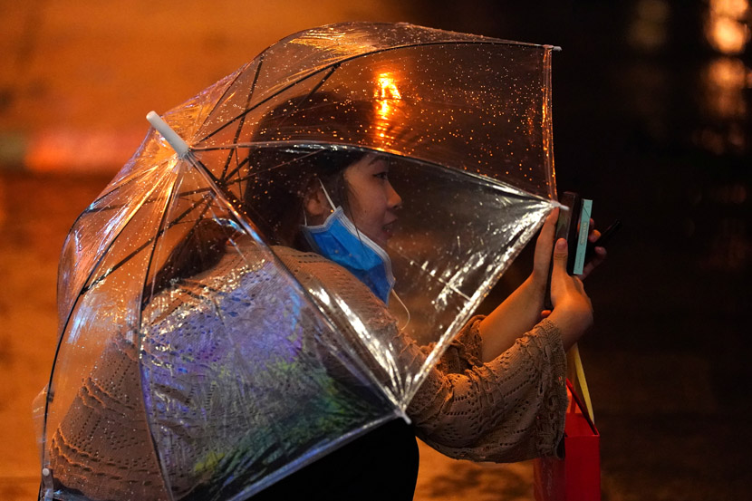 A woman juggles phone, umbrella, and mask on a rainy day in Beijing, Aug. 12, 2020. Tingshu Wang/People Visual