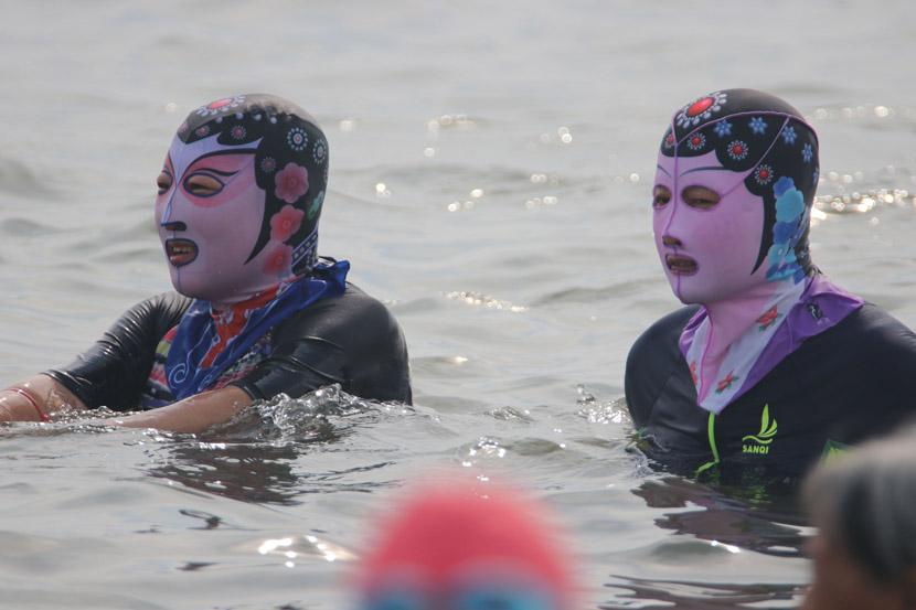 """Beachgoers in """"facekinis"""" enjoy the waters in Qingdao, Shandong province, Aug. 15, 2020.  Huang Jiexian/People Visual"""