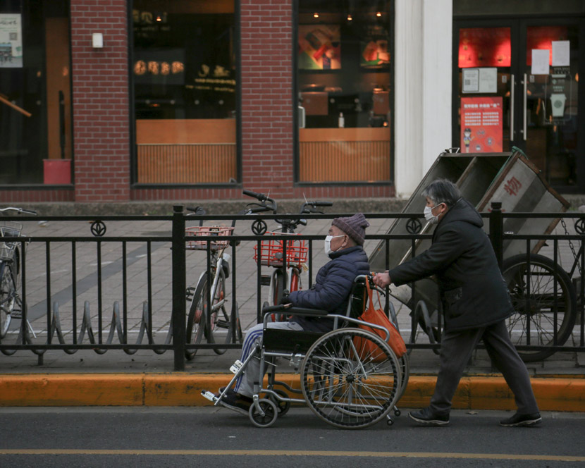 An elderly woman pushes a man in a wheelchair down a street in Shanghai, March 5, 2020. Jin Xiaoxin/People Visual