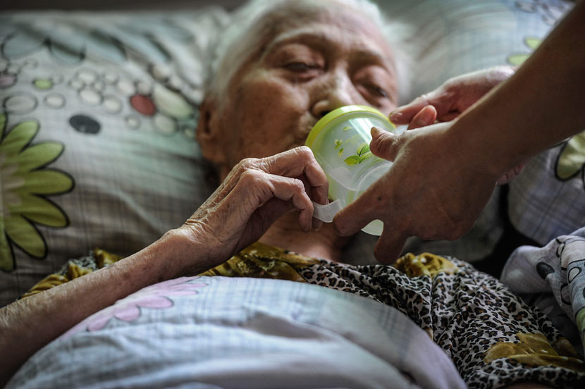 An elderly woman drinks from a cup with the help of a staff member at a nursing home in Zhongshan, Guangdong province, Oct. 9, 2013. Ye Zhiwen/VCG