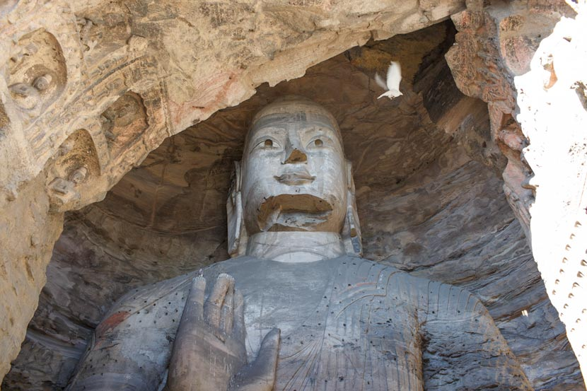 Across the highway from the Jinhuagong coal mine, Buddha statues at the Yungang Grottoes witness the changes in Datong, Shanxi province, Nov. 7, 2016. Zhou Pinglang/Sixth Tone