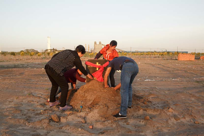 Members of a Christian church dig in the soil to uncover the cornerstone at their new church site in Tongliao, Inner Mongolia Autonomous Region, May 29, 2017. Zhou Pinglang/Sixth Tone