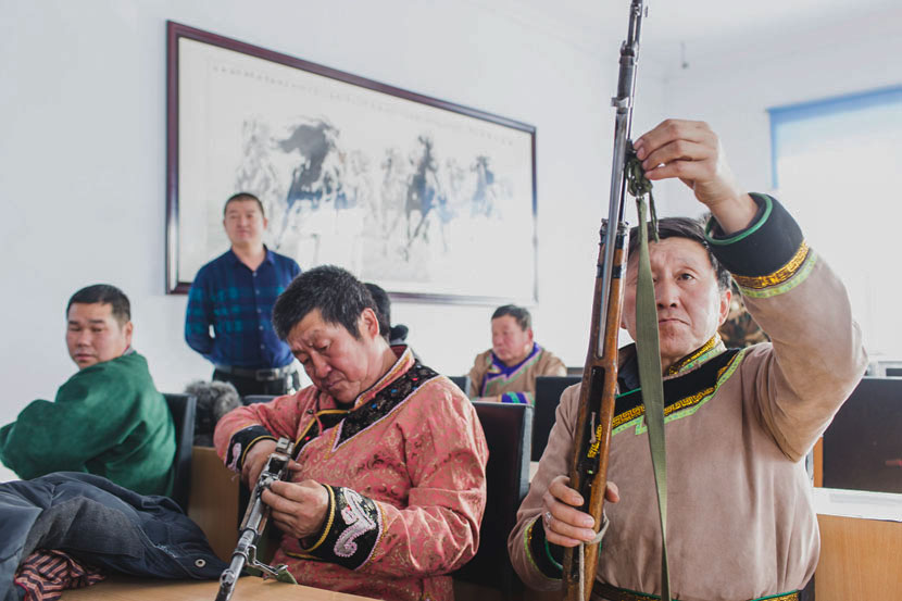 Hunters check their rifles in the meeting room of the local government in Xinsheng Township, Heihe, Heilongjiang province, Nov. 22, 2016. Zhou Pinglang/Sixth Tone