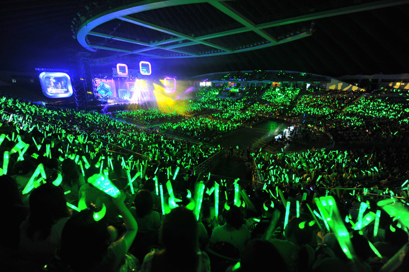 Fans of Zhou Bichang wave green glow sticks during a concert in Guangzhou, Guangdong province, May 29, 2010. Chen Zhongqiu for Sixth Tone