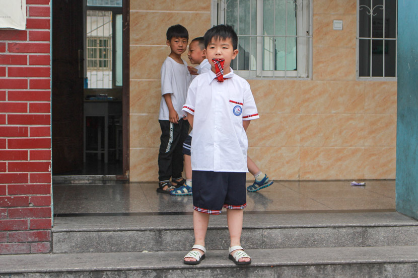 A boy plays with his uniform tie at Pingqiao No. 2 Primary School in Xinyang, Henan province, June 15, 2017. Wang Yiwei/Sixth Tone