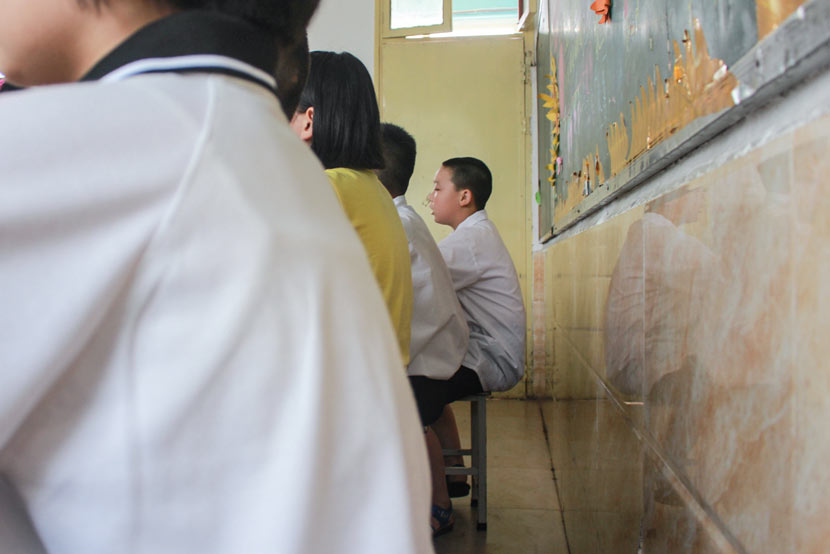 The last row of students lines the back wall of a classroom at Pingqiao No. 2 Primary School in Xinyang, Henan province, June 15, 2017. Wang Yiwei/Sixth Tone