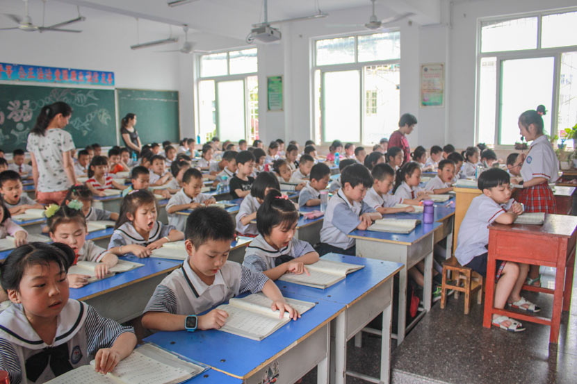 Students read aloud from a textbook in a classroom at Pingqiao No. 2 Primary School in Xinyang, Henan province, June 15, 2017. Wang Yiwei/Sixth Tone