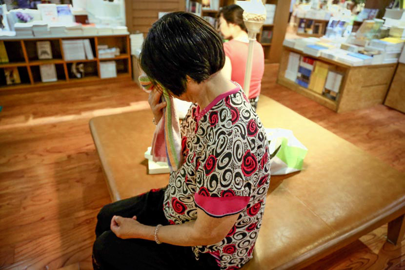 Yan Zhaofeng wipes away tears as she shares her background at Xinhua Bookstore in Hefei, Anhui province, July 15, 2017. Guo Quanzhi/Sixth Tone