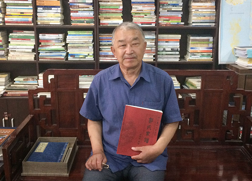 Guo Yiping holds a published copy of his family history at the offices of Tu Jincan's publishing company in Beijing, June 12, 2017. Zhang Liping/Sixth Tone