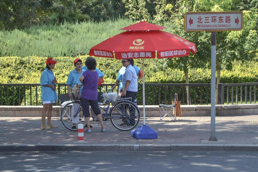 'Chaoyang Masses' volunteers converse near a guard station in Chaoyang District, Beijing, Aug. 31, 2015. Li Gang/IC