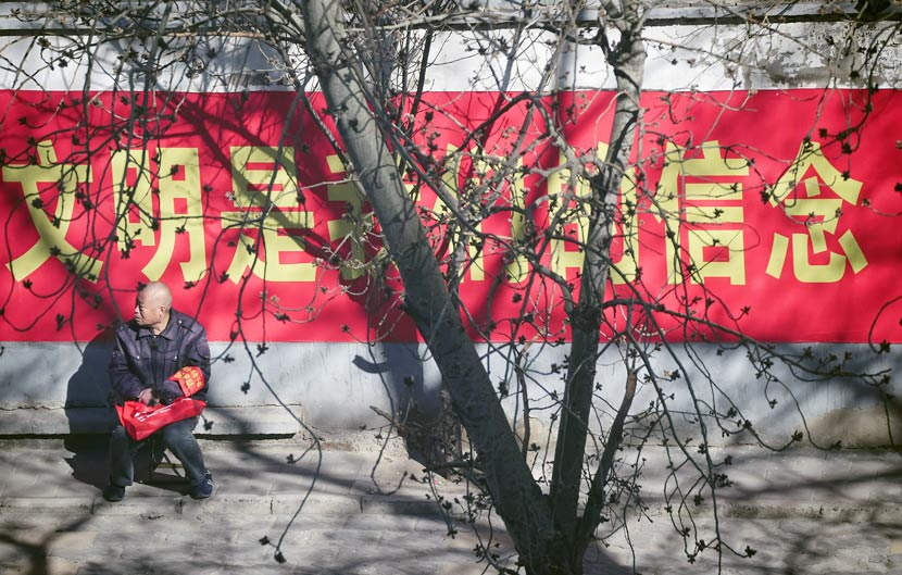 A volunteer guard takes a break in Chaoyang District, Beijing, March 7, 2016. Sha Lang/VCG