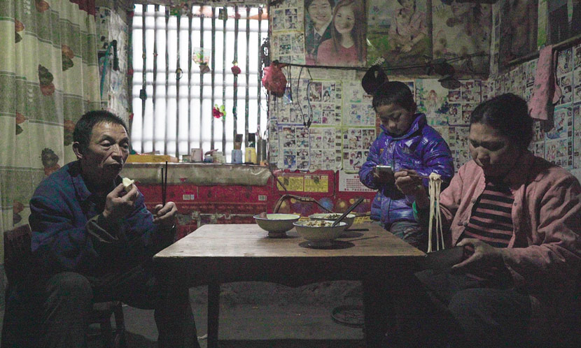 Huai Shengtang eats lunch with his wife and grandson at their old house in Qiyan Village, Ankang, Shaanxi province, March 11, 2017. Chen Xi/Sixth Tone
