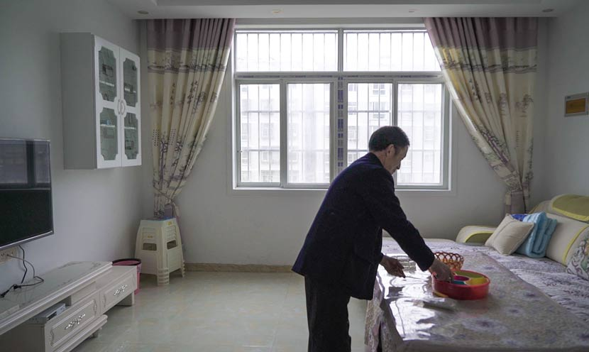 Huai Shengtang tidies his apartment in Qiyan New Village, Ankang, Shaanxi province, March 11, 2017. Chen Xi/Sixth Tone
