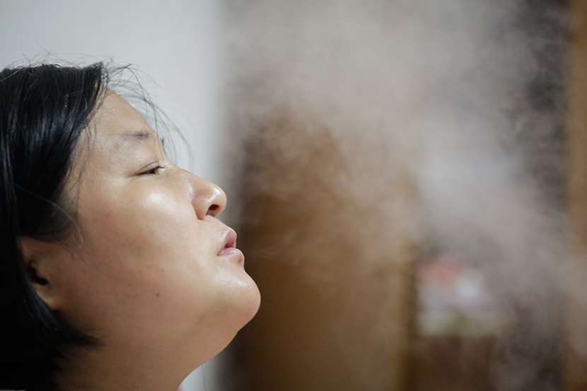 Sun Sulin breathes through the mist from a humidifier at home in Shanghai, July 6, 2017. Zhong Changqian/Sixth Tone