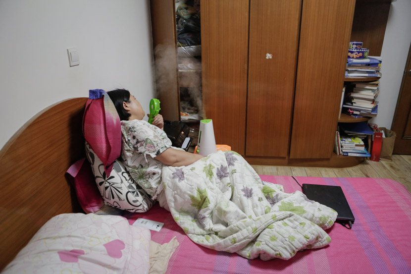 Sun Sulin uses a portable fan and a humidifier to help relieve her nasal symptoms at home in Shanghai, July 6, 2017. Zhong Changqian/Sixth Tone