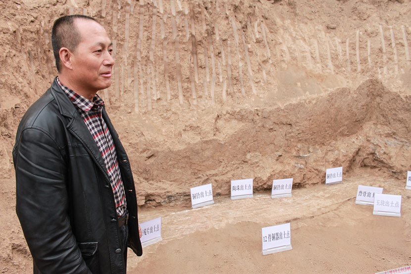 Wei Bingxiang stands by the artifact excavation site in his backyard in Weijiaya Village, Baoji, Shaanxi province, Oct. 22, 2014. Zhou Jinzhu/VCG