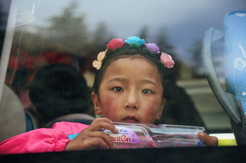 An ethnic Tibetan girl sits on a bus before being evacuated from Jiuzhaigou County, Sichuan province, Aug. 10, 2017. Xie Kuangshi/Sixth Tone