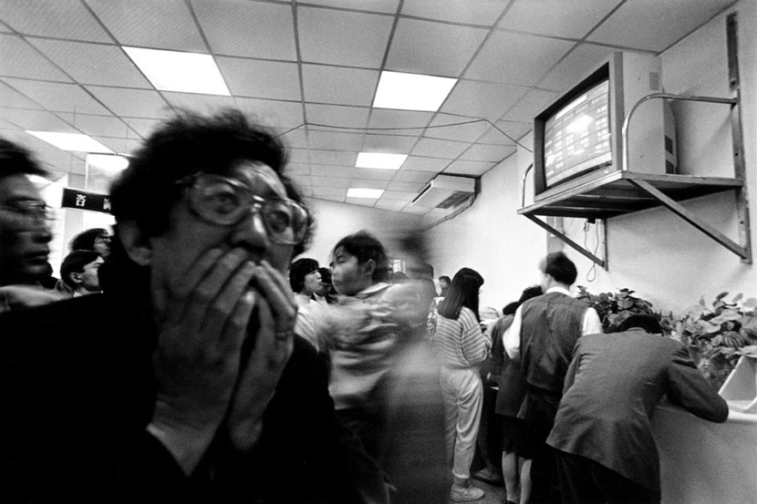 A man anxiously watches a monitor at a stock exchange in Shenzhen, Guangdong province, 1992. From Daken Art Center