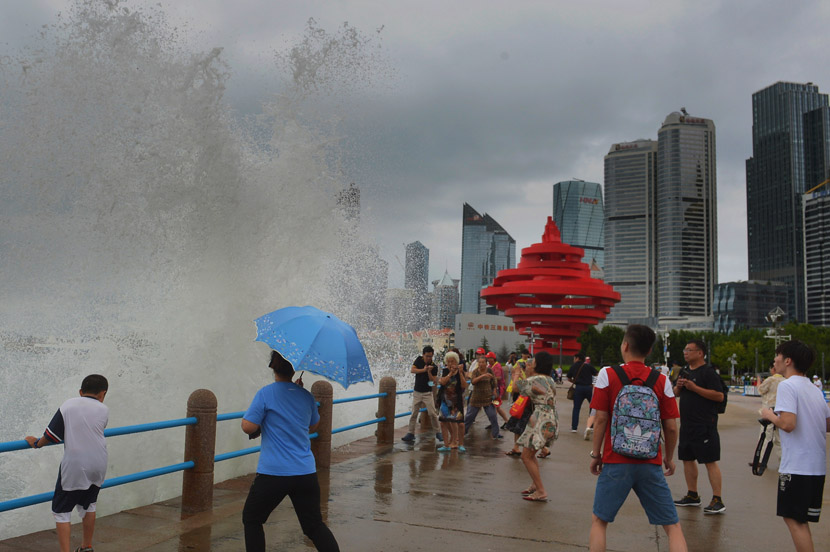 Pedestrians witness a large wave caused by Typhoon Bavi in Qingdao, Shandong province, Aug. 26, 2020. Wang Haibin/People Visual