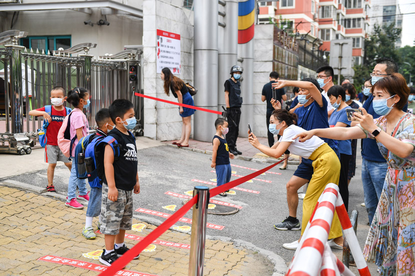 Parents take photos of their children in front of a primary school gate on their first day at school in Beijing, Aug. 29, 2020. People Visual