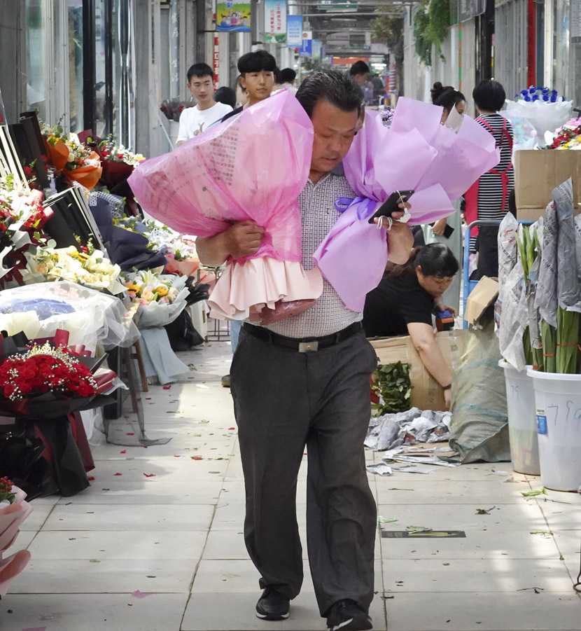 A vendor holds two bouquets of flowers during Qixi Festival at a flower market in Zhengzhou, Henan province, Aug. 25, 2020. Wang Zhongju/CNS/People Visual