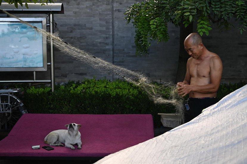 A resident repairs his fishing net while his pet dog watches in Beijing, Aug. 27, 2020. Cui Nan/CNS/People Visual