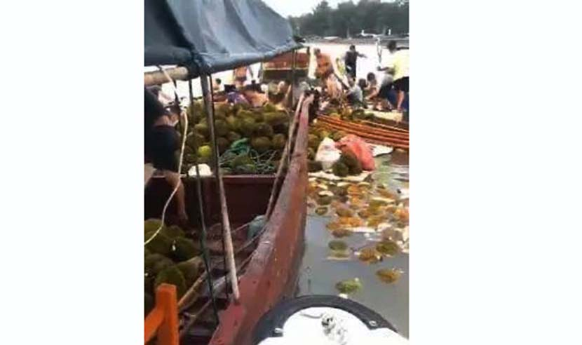 A video screenshot shows villagers collecting tainted durians from a boat on a beach near Dongxing, Guangxi Zhuang Autonomous Region, Aug. 26, 2020. From Weibo