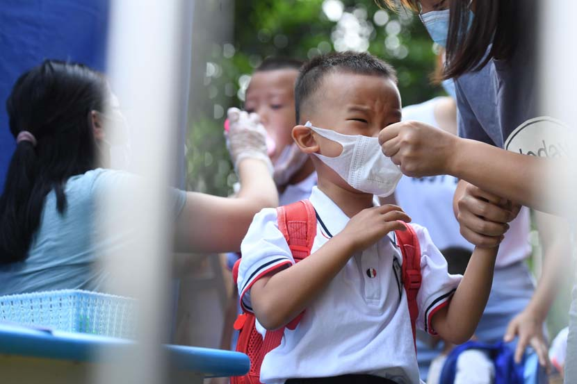 A mother helps her son wear a face mask correctly on the child's first day of school in Chongqing, Sept. 1, 2020. Chen Chao/CNS/People Visual