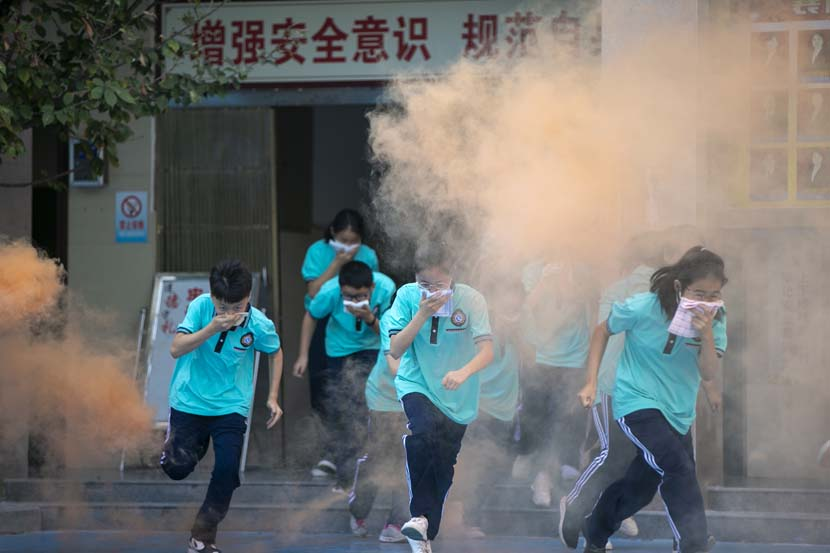 Students cover their faces as they evacuate a building during a fire drill at a high school in Xiangyang, Hubei province, Sept. 3, 2020. Su Xiaojie/People Visual