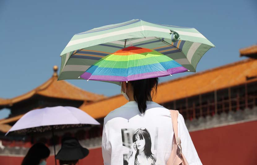 A tourist protects herself from the sun while visiting the Forbidden City in Beijing, Sept. 5, 2020. People Visual