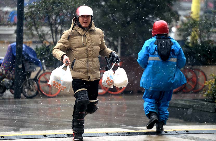 A food-delivery worker runs to complete an order in Jinan, Shandong province, Dec. 24, 2017. People Visual