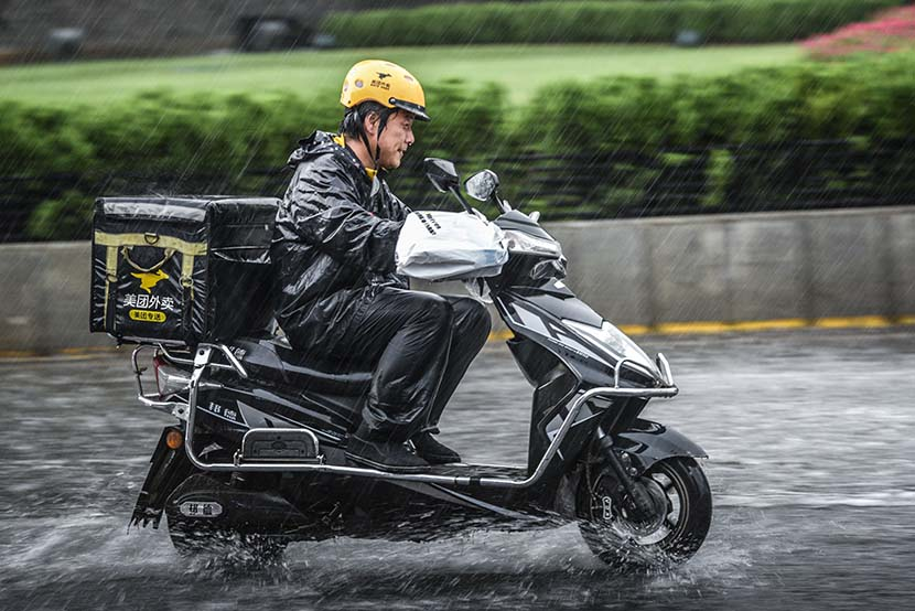 A Meituan courier delivers takeout orders on a rainy day in Xi'an, Shaanxi province, July 26, 2018. People Visual