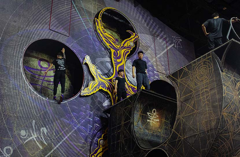 "Three acrobats practice a ""trampowall"" act backstage at the Xintiandi Group Sun Theater in Hangzhou, Zhejiang province, July 8, 2020. As foreign acrobats specializing in trampoline stunts have been unable to reenter China, temporary local artists were hired to create a simplified version of the routine. Kenrick Davis/Sixth Tone"