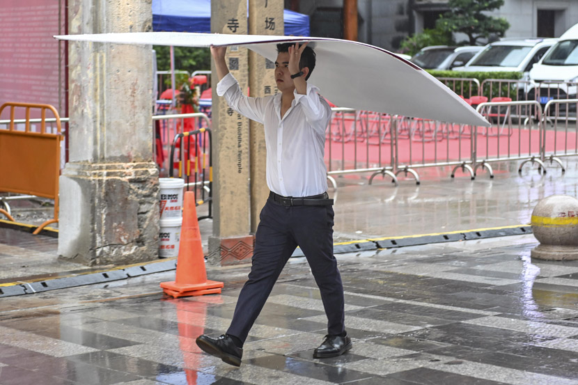A man holds a plastic sheet to shelter from rain in Guangzhou, Guangdong province, Sept. 8, 2020. Chen Jimin/CNS/People Visual