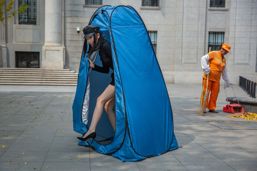 A model walks out of a changing tent, while a street cleaner sweeps in Wuhan, Hubei province, Sept. 8, 2020. Chen Zhongqiu/People Visual