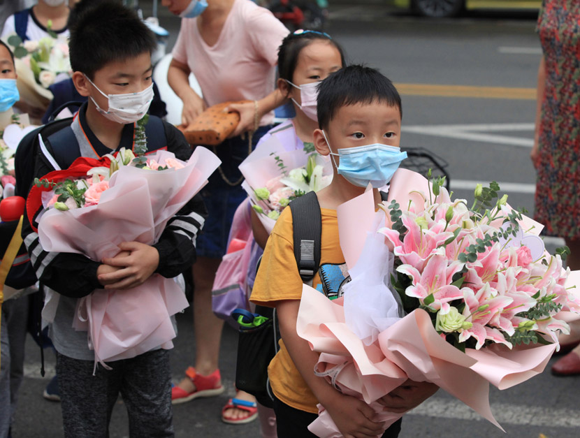 Primary school children hold flower bouquets for their teachers to mark Chinese Teachers' Day in Nanjing, Jiangsu province, Sept. 10, 2020. People Visual