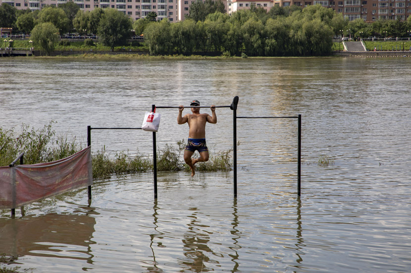A man exercises at a flooded playground near Songhua River in Jilin province, Sept. 11, 2020. Zhu Wanchang/People Visual