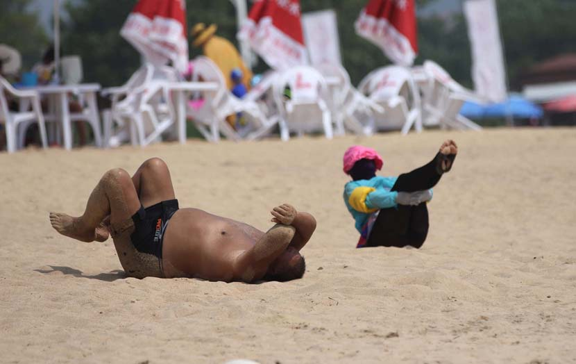 Tourists relax in the First Bathing Beach in Qingdao, Shandong province, Aug. 18, 2020. People Visual