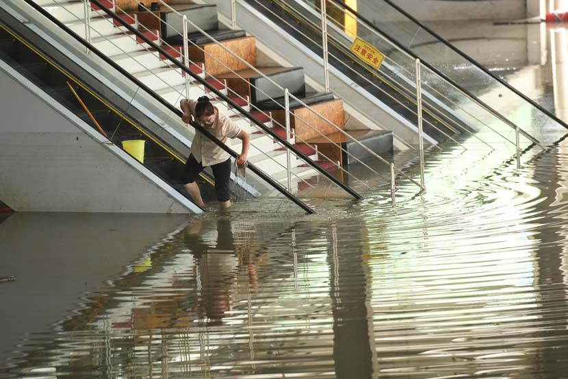 A cleaner washes an escalator in Chongqing, Aug. 21, 2020. Chen Chao/CNS/People Visual