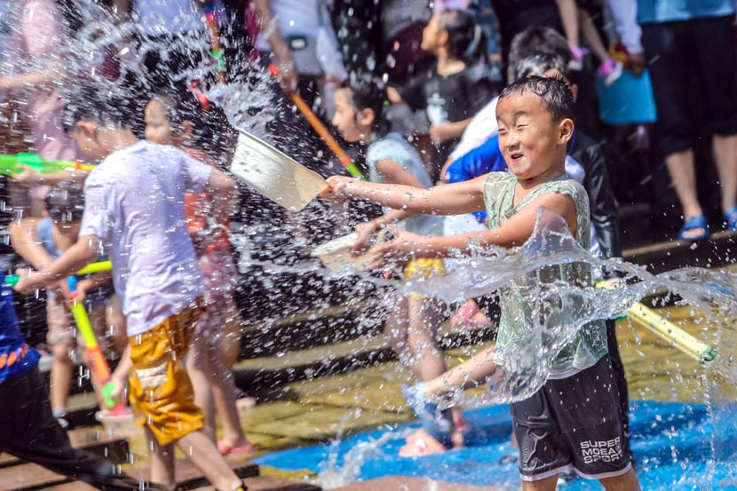 Children play with water during a water-splashing event in Jinan, Shandong province, Aug. 22, 2020. People Visual