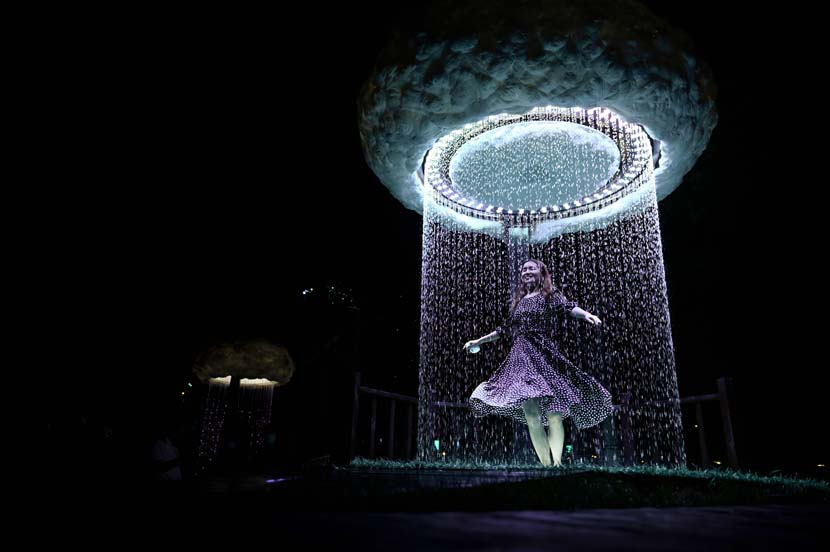A woman dances as she visits an immersive outdoor light exhibition during the 2020 Beijing International Light Festival at a park in Beijing, Aug. 22, 2020. Wang Zhao/People Visual