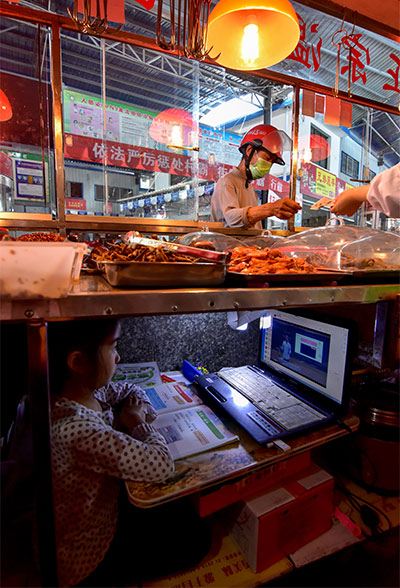 A girl attends an the online class under the table of her mother's stand at a wet market in Yuyangguan Town, Hubei province, April 29, 2020. People Visual