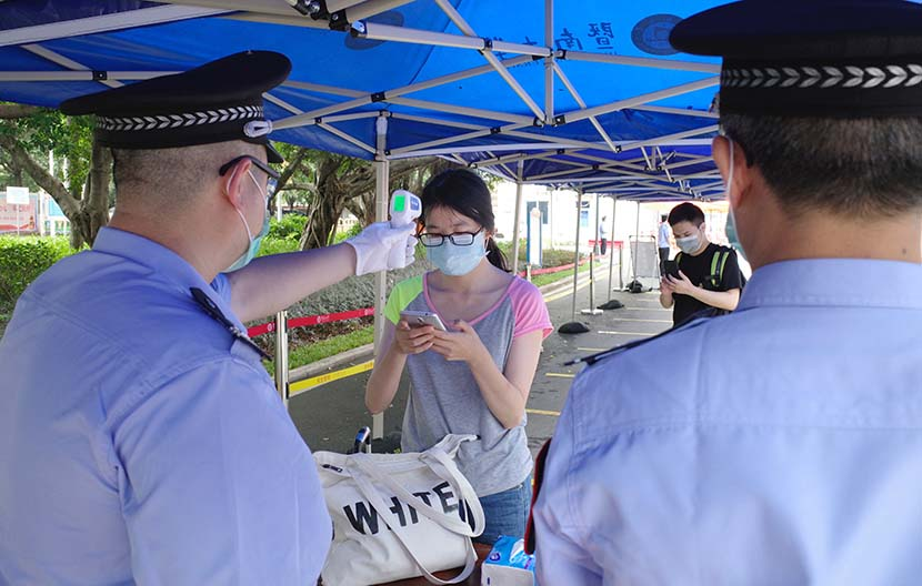 A student gets her temperature checked entering the campus of Jinan University in Guangzhou, Guangdong province, May 11, 2020. People Visual
