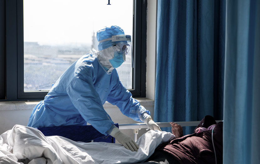 A medical worker takes care of a patient during the outbreak at Wuhan Union Hospital in Wuhan, Hubei province, Feb. 20, 2020. Xu Hao/Southern Daily/People Visual