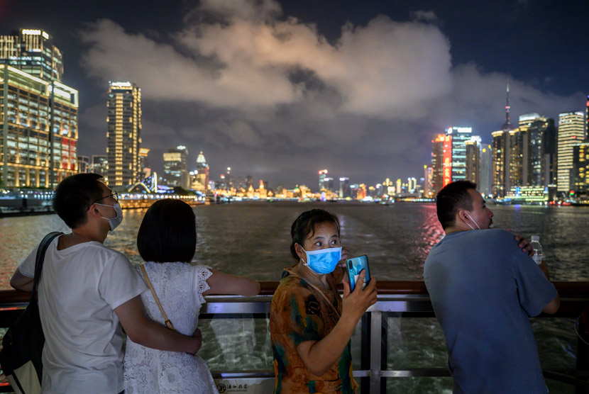 A woman wearing a face mask takes photos on the deck of a tourist boat on the Huangpu River in Shanghai, Sept. 1, 2020. Kevin Frayer/People Visual