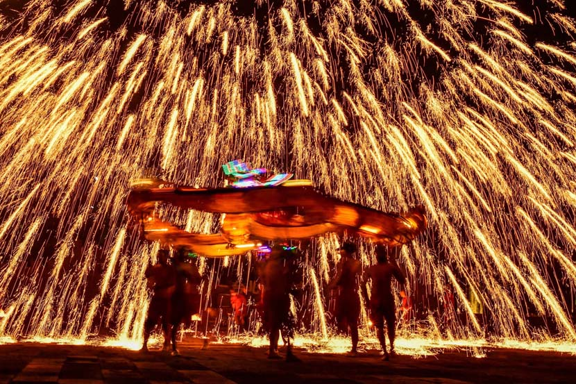 """Folk artists perform the """"fire dragon, steel flower"""" dance in the historical district of Zaozhuang, Shandong province, Oct. 1, 2020. People Visual"""