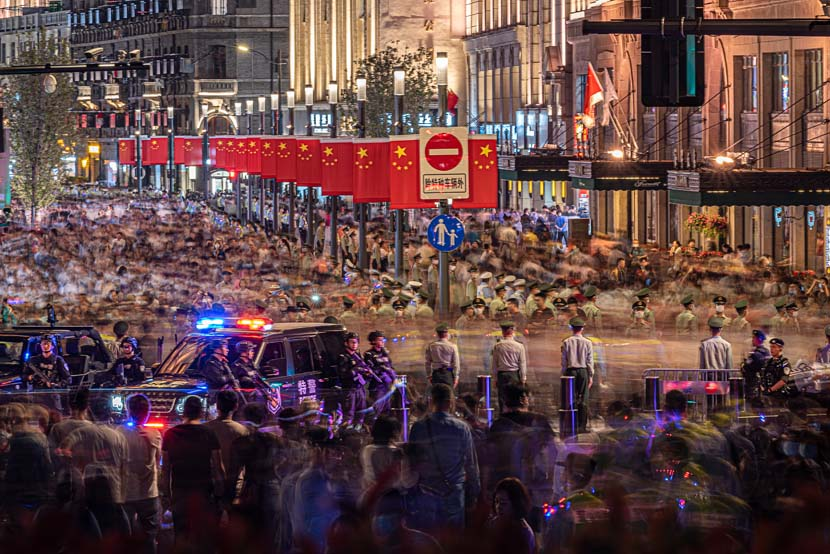 Police officers maintain order in the streets as tourists gather to watch a light show for the National Day holiday in Shanghai, Sept. 30, 2020. People Visual